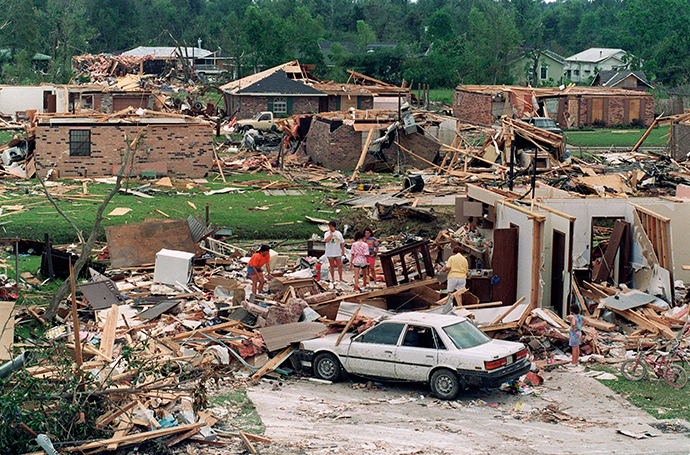 A group of people sift 28 August 1992 through the rubble of a house that was directly in the path of a 26 August tornado spawned by Hurricane Andrew (AFP Photo)