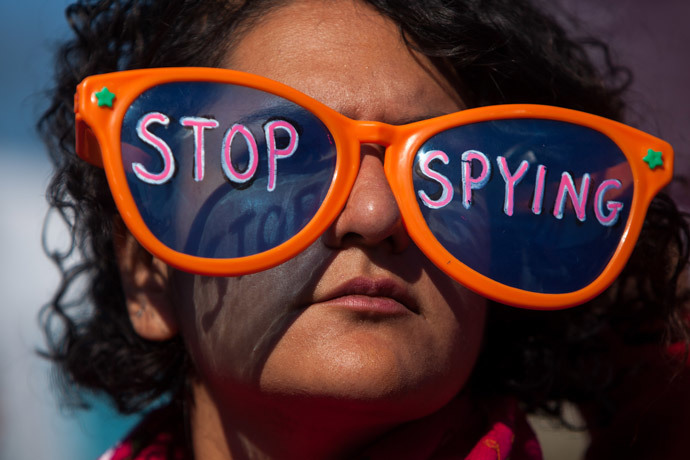 "A woman wearing oversized sunglasses lettered with the words ""stop spying"" listens to speakers during the Stop Watching Us Rally protesting surveillance by the U.S. National Security Agency, on October 26, 2013, in front of the U.S. Capitol building in Washington, D.C.(AFP Photo / Allison Shelley)"