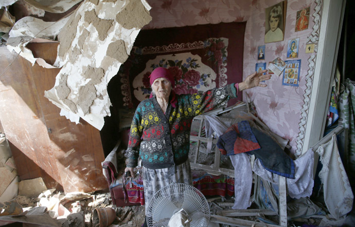 Zinaida Patskan, 80, speaks as she stands inside her home which was destroyed by Ukrainian artillery, on the outskirts of the eastern Ukrainian town of Slaviansk May 22, 2014. (Reuters/Maxim Zmeyev)