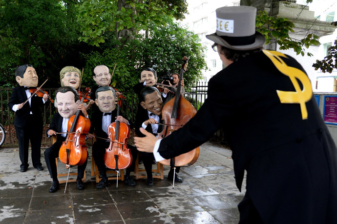 Oxfam charity activists wearing masks depicting G7 leaders protest on the sidelines of the G7 summit in front of European Council headquarters in Brussels, on June 4, 2014. (AFP Photo/Thierry Charlier)