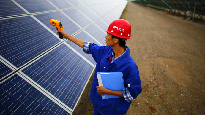 A worker inspects solar panels at a solar farm in Dunhuang, 950km (590 miles) northwest of Lanzhou, Gansu Province (Reuters/Carlos Barria)