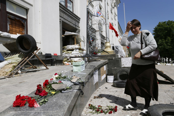 A woman places flowers near the site of an explosion in a regional administration building in the eastern Ukrainian city of Luhansk June 3, 2014. (Reuters/Gleb Garanich)
