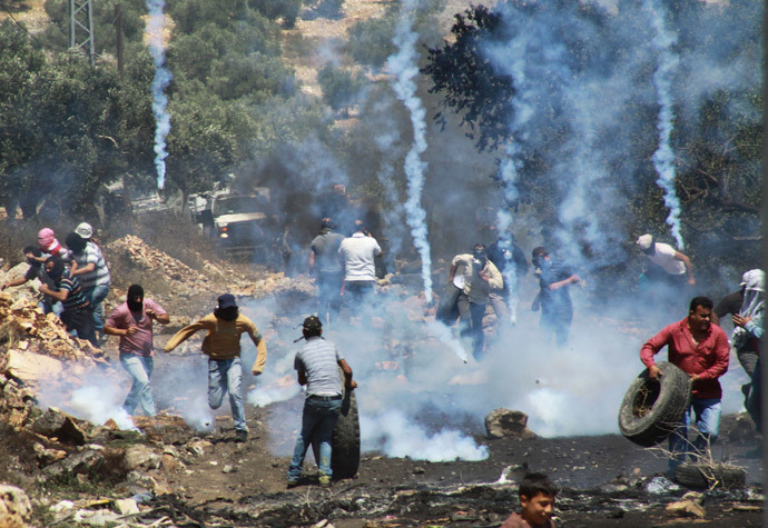 Palestinian protesters run away from tear gas fired by Israeli soldiers during clashes following a protest against the Jewish settlement of Qadomem, in the West Bank village of Kofr Qadom near Nablus May 23, 2014. (Reuters / Abed Omar Qusini)