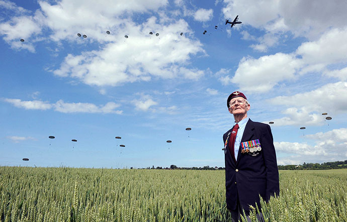British WWII veteran Frederik Glover stands in a corn field as soldiers parachute down during a D-Day commemoration in northern France on June 5 2014. (AFP Photo / Thomas Bregardis)