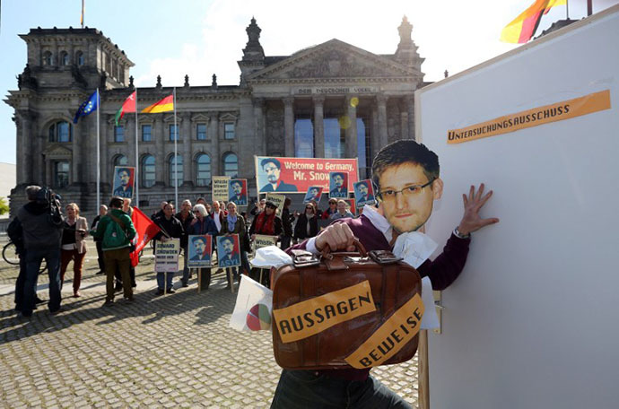 "An activist wearing a mask of fugitive US intelligence leaker Edward Snowden tries to get past a door reading ""Investigation Committee"" while holding a suitcase reading ""Evidence"" during a demonstration in favor of an appearance by Snowden as a witness in German NSA hearings held in the German Bundestag, or lower house of parliament, outside the Reichstag building in Berlin on May 8, 2014. (AFP Photo / Adam Berry)"