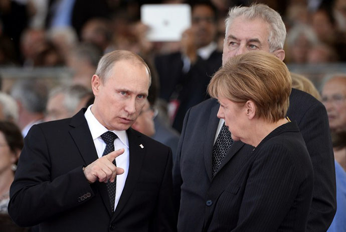 Russian President Vladimir Putin and German Chancellor Angela Merkel chat at the international D-Day commemoration ceremony in Normandy, on June 6, 2014, marking the 70th anniversary of the World War II Allied landings in Normandy. (AFP Photo / Alain Jocard)