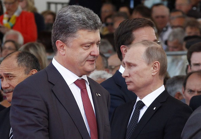 Ukraine's President-elect Petro Poroshenko (L) walks past Russian President Vladimir Putin during an international D-Day commemoration ceremony on the beach of Ouistreham, Normandy, on June 6, 2014, marking the 70th anniversary of the World War II Allied landings in Normandy. (AFP Photo / Christophe Ena)
