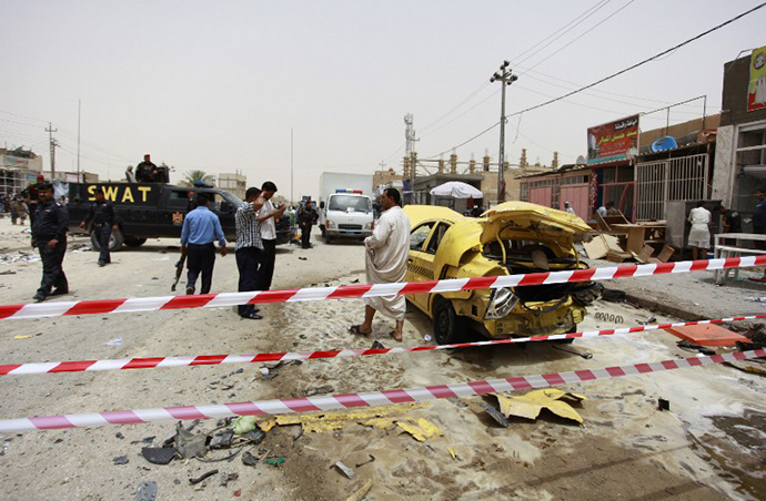 Iraqis inspect the site of a car bomb explosion that targeted a market in the central shrine city of Najaf on June 2, 2014, killing at least one person and wounding 20 others. (AFP Photo / Haidar Hamdani)