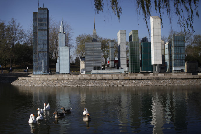 A flock of ducks swam pass the mini replica of Manhattan buildings in Beijing World Park, in the southwestern suburb of Beijing.(AFP Photo / China Out)