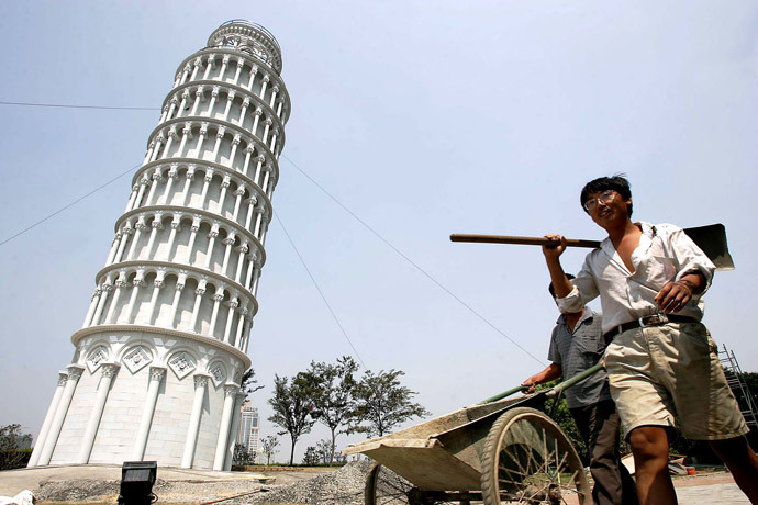 Chinese workers walk past a 1:4 scale mini leaning tower of Pisa in Shanghai (Reuters / China Photos ASW / TW)