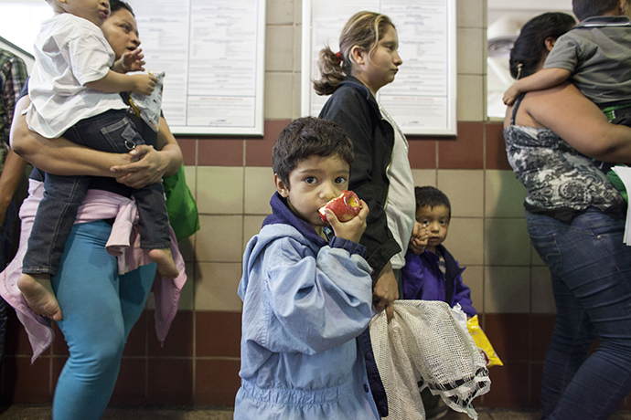 Migrants, consisting of mostly women and children, who just disembarked from a U.S. Immigration and Customs Enforcement (ICE) bus wait for a Greyhound official to process their tickets to their next destination at a Greyhound bus station in Phoenix, Arizona May 29, 2014. (Reuters / Samantha Sais)