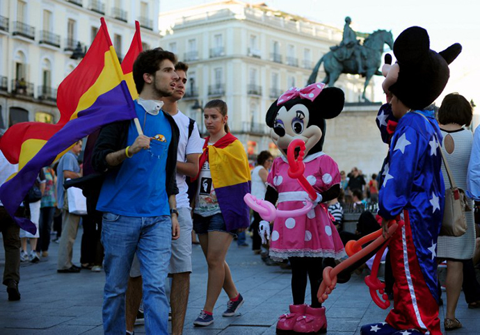 Protesters holding flags of the Spanish Second Republic walk past people dressed up as cartoon characters during a demonstration to demand a referendum on the monarchy following the abdication of King Juan Carlos, in Madrid on June 7, 2014. (AFP Photo / Tom Gandolfini)