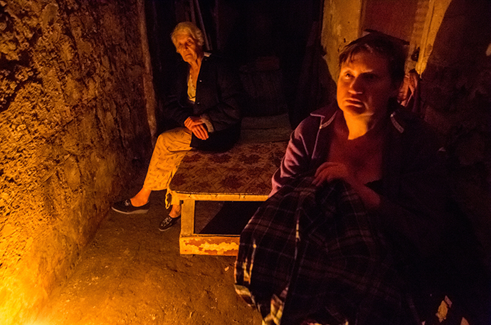 Residents of Slavyansk take shelter in the basement of their house during a heavy artillery shelling of their city on June 8, 2014. (RIA Novosti / Andrey Stenin)