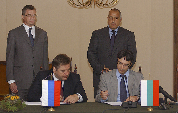 Bulgarian former Prime Minister Boiko Borisov (rear R) and Russia's Gazprom Deputy Chairman Alexander Medvedev (rear L) watch as Bulgarian former Economy and Energy Minister Traicho Traikov (front R) and Russia's former Energy Minister Sergei Shmatko sign documents during an official ceremony in the city of Varna, some 450km (280miles) north-east of Sofia July 17, 2010. (Reuters)