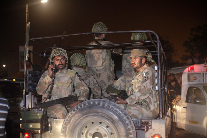 Pakistan Army soldiers sit on a vehicle as they arrive at Jinnah International Airport in Karachi June 9, 2014. (Reuters/Athar Hussain)