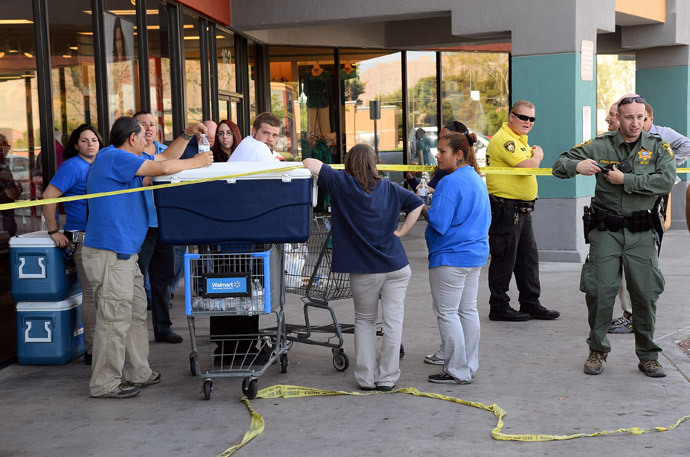 Las Vegas Metropolitan Police Department officers stand near Wal-Mart employees near their store on June 8, 2014 in Las Vegas, Nevada.(AFP Photo / Ethan Miller)