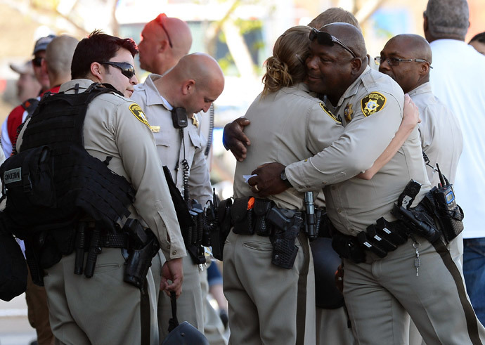 Las Vegas Metropolitan Police Department officers hug near a Wal-Mart on June 8, 2014 in Las Vegas, Nevada. (AFP Photo / Ethan Miller)