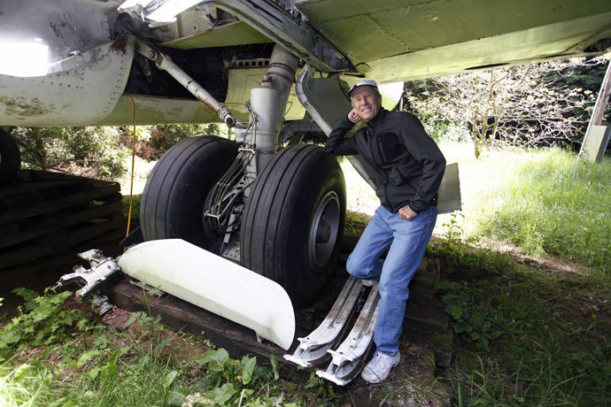 Bruce Campbell leans on a tyre of his Boeing 727 home in the woods outside the suburbs of Portland, Oregon May 21, 2014. (Reuters/Steve Dipaola)