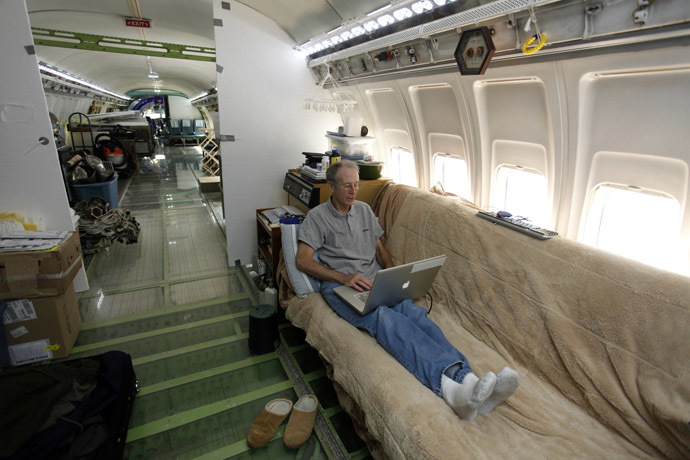 Bruce Campbell sits on his futon bed while using a laptop in his Boeing 727 home in the woods outside the suburbs of Portland, Oregon May 21, 2014. (Reuters/Steve Dipaola)