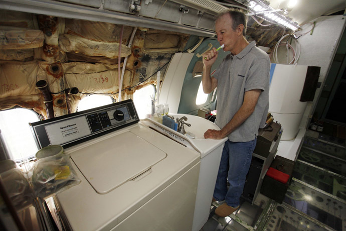 Bruce Campbell brushes his teeth at a sink in his Boeing 727 home in the woods outside the suburbs of Portland, Oregon May 21, 2014. (Reuters/Steve Dipaola)