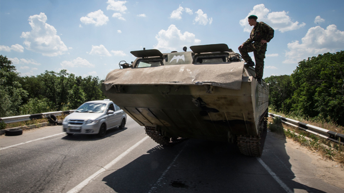 A self-defense fighter looks on from an amphibious vehicle near a road check point outside the eastern Ukrainian city of Lugansk June 8, 2014 (Reuters / Shamil Zhumatov)