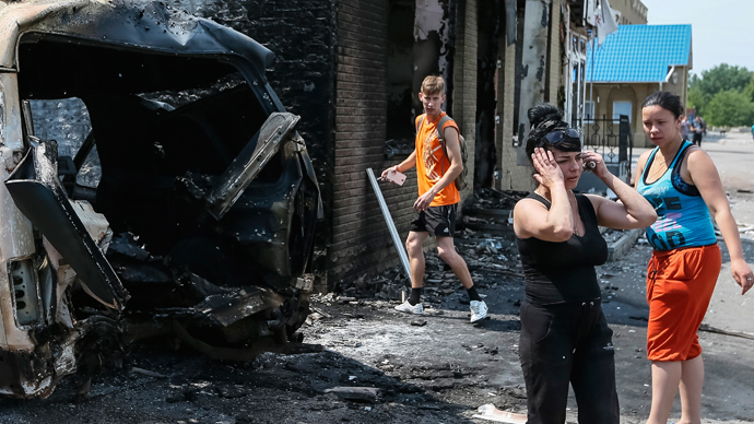 Local residents react as they stand near destroyed houses and vehicles in the eastern Ukrainian town of Slavyansk June 9, 2014 (Reuters / Gleb Garanich)