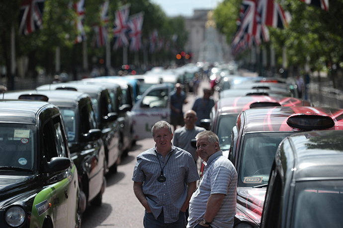 London black cab drivers take part in a protest against a new private taxi service 'Uber', a mobile phone app, on the Mall leading to Buckingham Palace in central London on June 11, 2014. (AFP Photo / Carl Court)