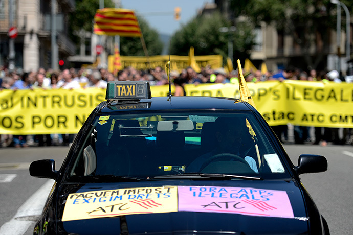 A taxi preceeds demonstrators holding a banner during a strike action in protest of unliscensed taxi-type-services in Barcelona on June 11, 2014. (AFP Photo / Josep Lago)