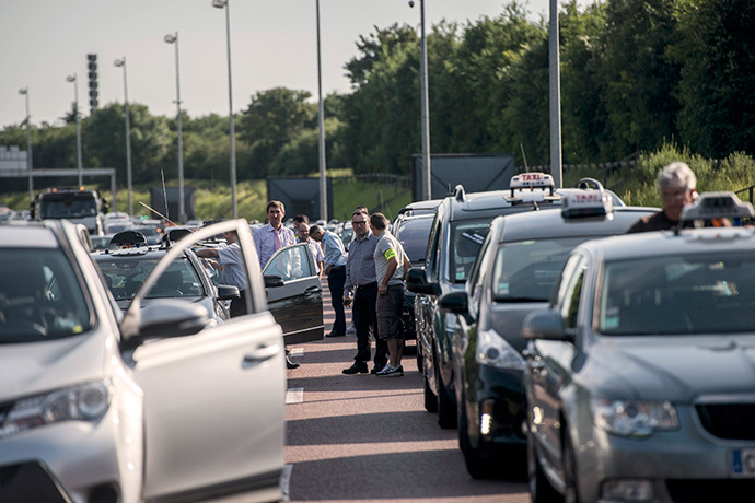 "Taxis drivers block highway outside Paris, near Roissy on June 11, 2014, as they take part in a demonstration to protest against the growing number of minicabs, known in France as ""Voitures de Tourisme avec Chauffeurs"" (VTC). (AFP Photo / Fred Dufour)"