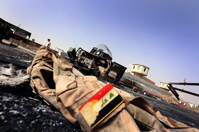 The jacket belonging to an Iraqi Army uniform lies on the ground in front of the remains of a burnt out Iraqi army vehicle close to the Kukjali Iraqi Army checkpoint, some 10km of east of the northern city of Mosul, on June 11, 2014. (AFP Photo / Safin Hamed)