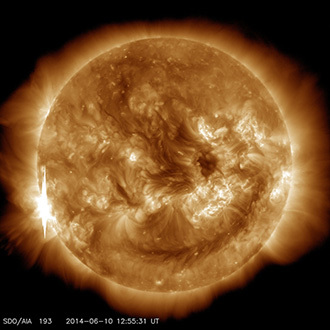 The second X-class flare of June 10, 2014, appears as a bright flash on the left side of this image from NASA's Solar Dynamics Observatory. This image shows light in the 193-angstrom wavelength, which is typically colorized in yellow. It was captured at 8:55 a.m EDT, just after the flare peaked. (Image Credit: NASA / SDO)