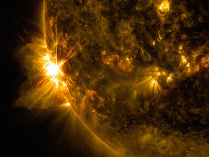 A solar flare bursts off the left limb of the sun in this image captured by NASA's Solar Dynamics Observatory on June 10, 2014, at 7:41 a.m. EDT. This is classified as an X2.2 flare, shown in a blend of two wavelengths of light: 171 and 131 angstroms, colorized in gold and red, respectively. (Image Credit: NASA / SDO / Goddard / Wiessinger)