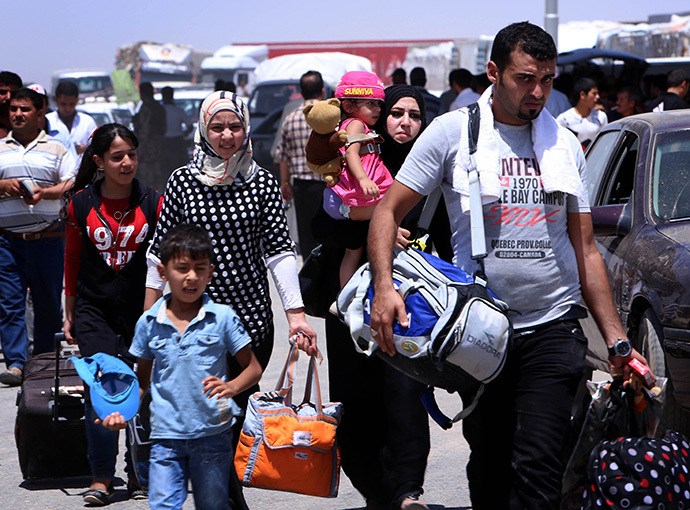 Iraqi families fleeing violence in the northern Nineveh province gather at a Kurdish checkpoint in Aski kalak, 40 kms West of Arbil, in the autonomous Kurdistan region (AFP Photo / Safin Hamed)