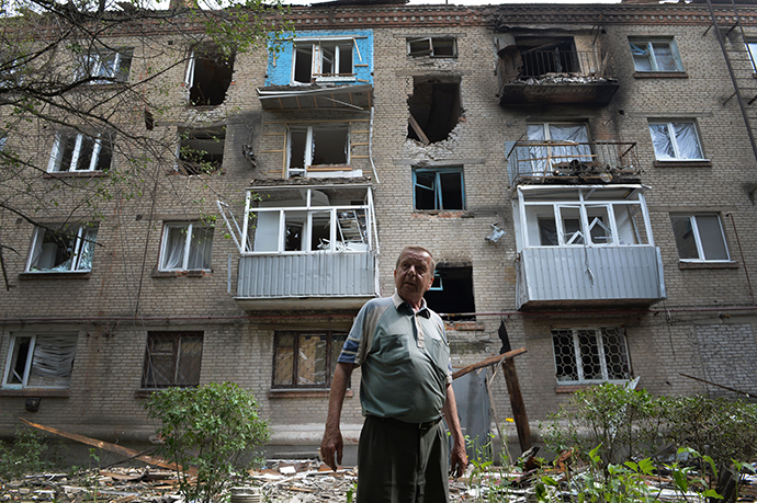 A local resident stands in front of the blown out windows and walls of a residential building after it was hit by mortar shells during clashes in the eastern Ukrainian city of Slavyansk, on June 11, 2014. (AFP Photo / Daniel Mihailescu)