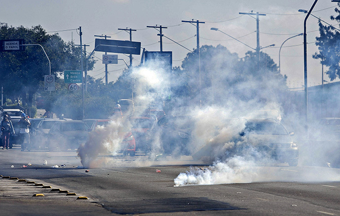 Tear gas grenades explode among cars during an anti-World Cup protest, on the morning the Brazilian mega-city hosts the tournament's opening match, in Sao Paulo on June 12, 2014. (AFP Photo / Miguel Schincariol)