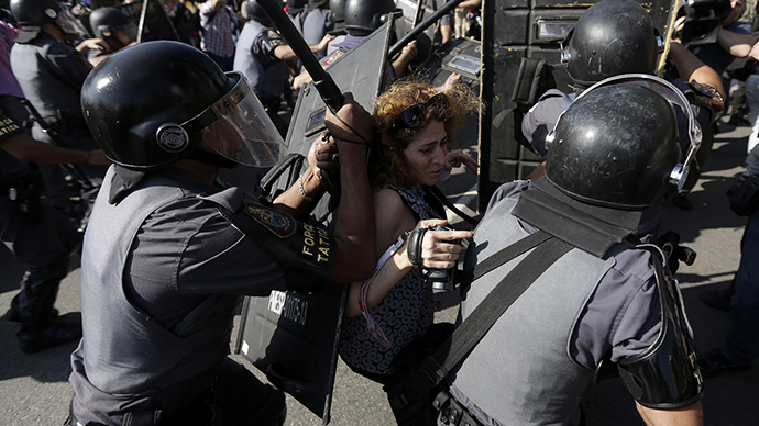 A woman is pushed by riot policemen during a clash with demontrators in a protest against the 2014 World Cup in Sao Paulo June 12, 2014. (Reuters / Ricardo Moraes)