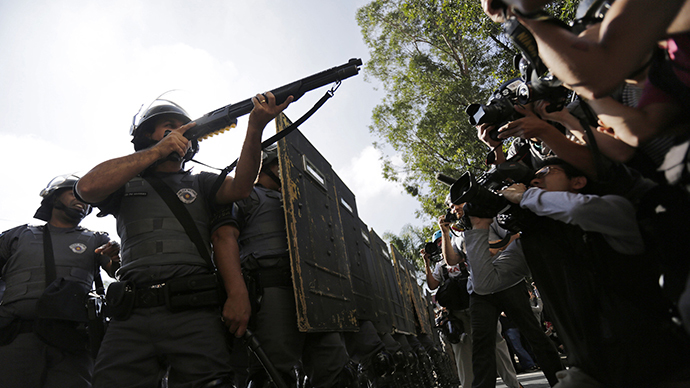 Members of the media film riot policemen during a protest against the 2014 World Cup in Sao Paulo June 12, 2014. (Reuters / Lunae Parracho)