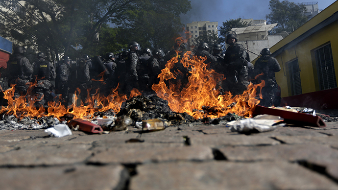 Riot policemen stand behind burning rubbish during a protest against the 2014 World Cup in Sao Paulo June 12, 2014. (Reuters / Ricardo Moraes)