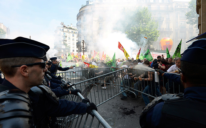 French riot police fire tear gas against protesters trying to move crowd control barriers during a demonstration by striking employees of the French state rail company SNCF near the Transport Ministry in Paris on June 12, 2014, on the second day of a nation-wide strike to protest a government railway reform project. (AFP Photo / Bertrand Guay)