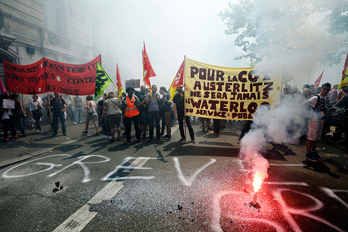 "Protesters hold a banner behind a burning flare reading ""For CGT, Austerlitz will never be the Waterloo of public service"" during a demonstration by striking employees of the French state rail company SNCF near the Transport Ministry in Paris on June 12, 2014, on the second day of a nation-wide strike to protest a government railway reform project. (AFP Photo / Bertrand Guay)"