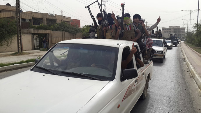 Fighters of the Islamic State of Iraq and the Levant (ISIL) celebrate on vehicles taken from Iraqi security forces, at a street in city of Mosul, June 12, 2014. (Reuters)