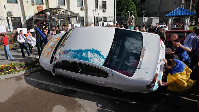 Pro-Ukrainian people overturn a car during a rally in front of the Russian embassy in Kiev June 14, 2014 (Reuters / Valentyn Ogirenko)
