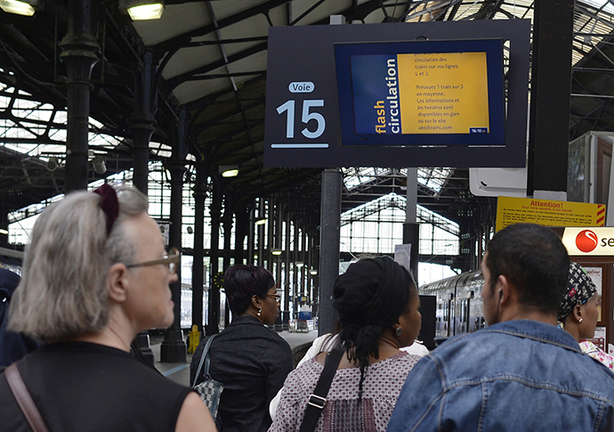 Travelers watch an information board announcing the trains that will be running, at the Gare Saint Lazare train station in Paris during a strike by SNCF railway company workers, on June 15, 2014. (AFP Photo / Miguel Medina)