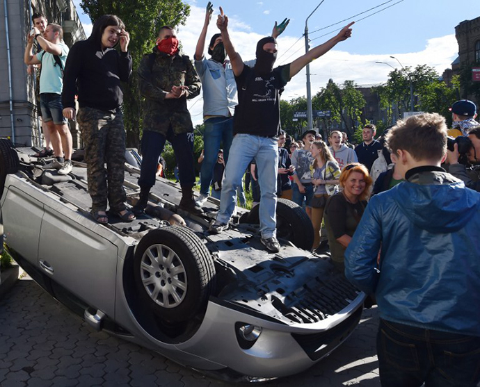 Demonstrators stand on an overturned car during a rally against the Russian president in front of the Russian embassy in Kiev on June 14, 2014. (AFP Photo / Sergei Supinsky)