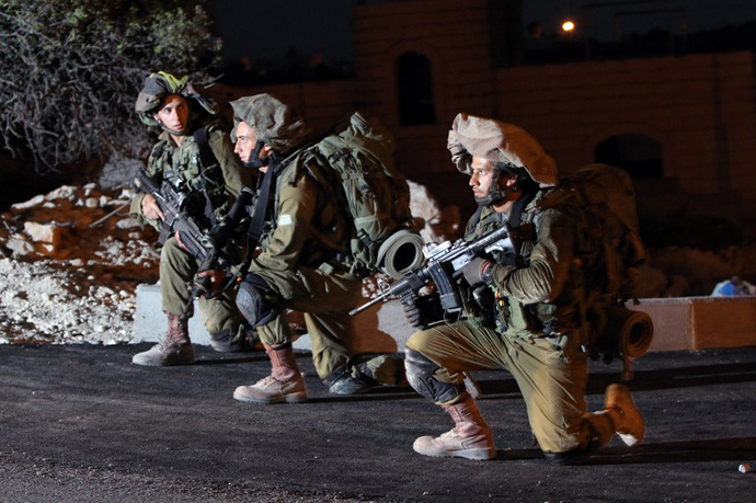 Israeli soldiers patrol an area in the West Bank town of Hebron on June 15, 2014, as they search for three teenagers who went missing near a West Bank settlement. (AFP Photo / Hazem Bader)