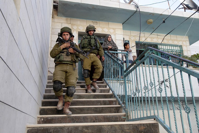 Israeli soldiers leave after inspecting a house where live Palestinians in the West Bank village of Tafoh, near Hebron on June 15, 2014, as they search for three teenagers who went missing near a West Bank settlement. (AFP Photo / Hazem Bader)