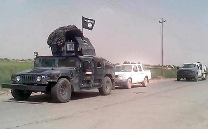Captured Iraqi security forces vehicles mounted with the trademark Jihadists flag as they drive along a road in the northern city of Mosul on June 12, 2014.(AFP Photo / Youtube / Harith)