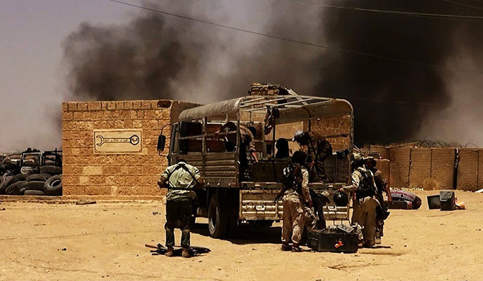 An image made available by the jihadist Twitter account Al-Baraka news on June 9, 2014 allegedly shows Islamic State of Iraq and the Levant (ISIL) militants taking position at a Iraqi border post on the Syrian-Iraqi border between the Iraqi Nineveh province and the Syrian town of Al-Hasakah. (AFP Photo)