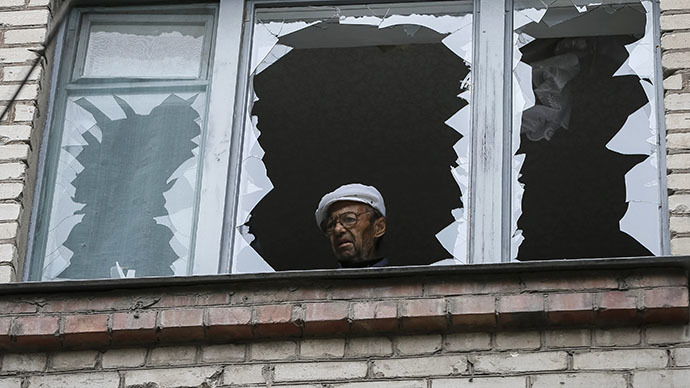 A man looks out of the broken window of his home in a residential building which was damaged by what locals say was overnight shelling by Ukrainian forces, in the eastern Ukrainian town of Slaviansk June 12, 2014. (Reuters / Gleb Garanich)