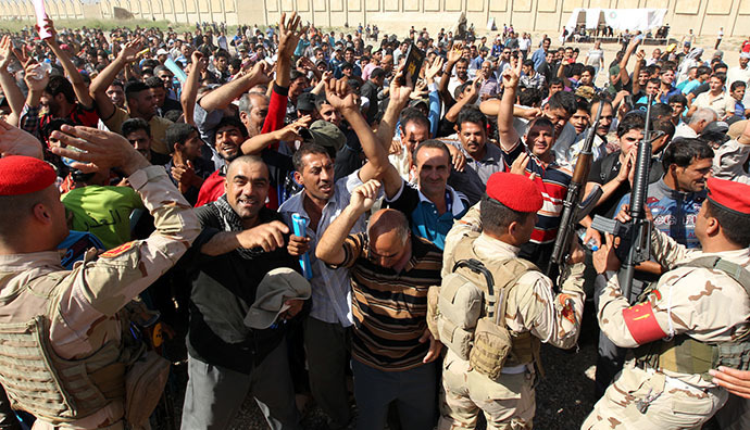 Iraqi men, who volunteered to fight against the Jihadist militants, gather around buses in Baghdad on June 13, 2014, as security forces are bolstering defenses in the capital. (AFP Photo / Sabah Arar)